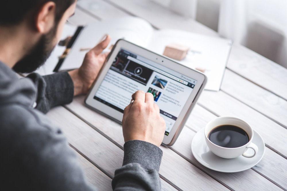 Мужчина читает новости на планшете