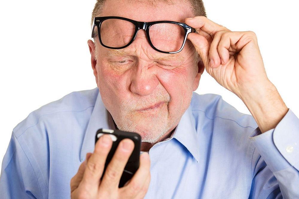 Пожилой мужчина жмурится, смотря в телефон