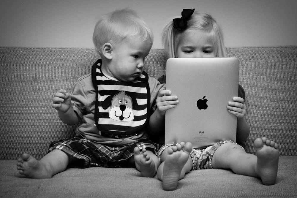 Дети сидят на диване с iPad