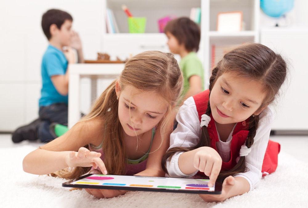 Две маленьких девочки с планшетом