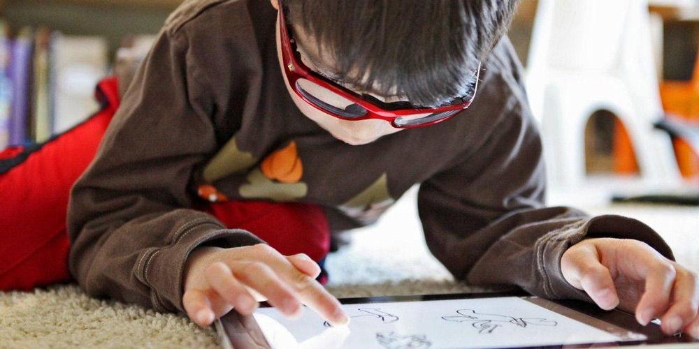 Ребенок с планшетом в красных очках
