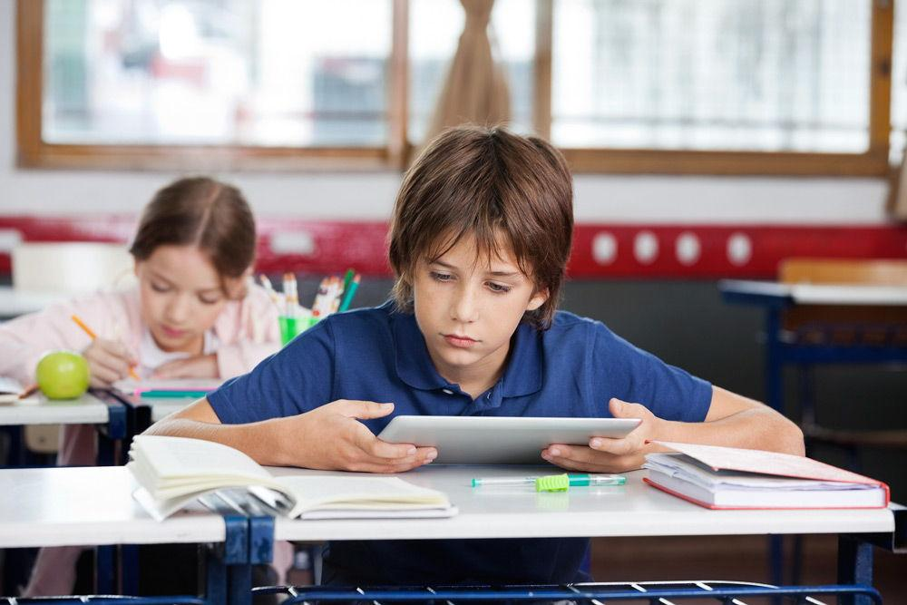 Школьник с планшетом сидит за столом