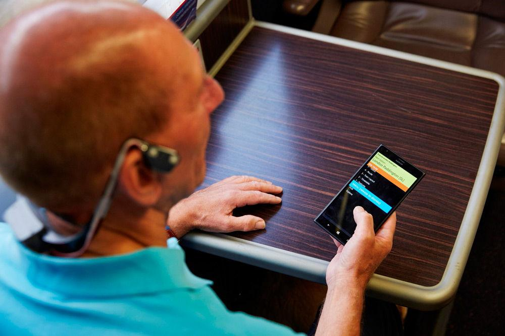 Пожилой незрячий мужчина сидит за столом со смартфоном
