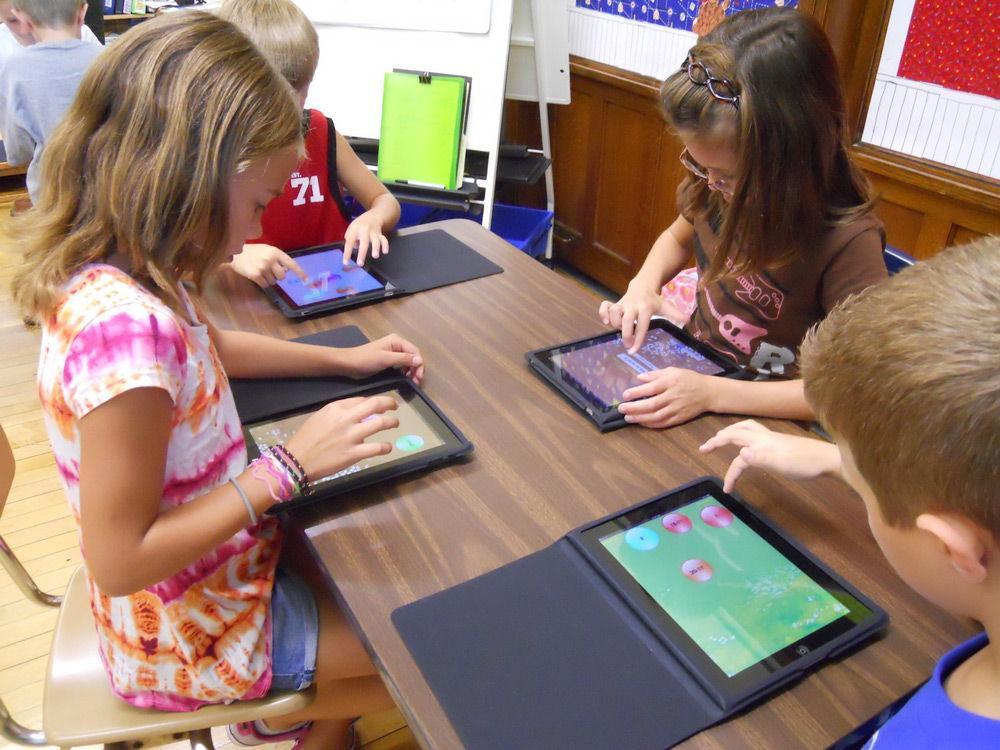 Дети играют в iPad за столом