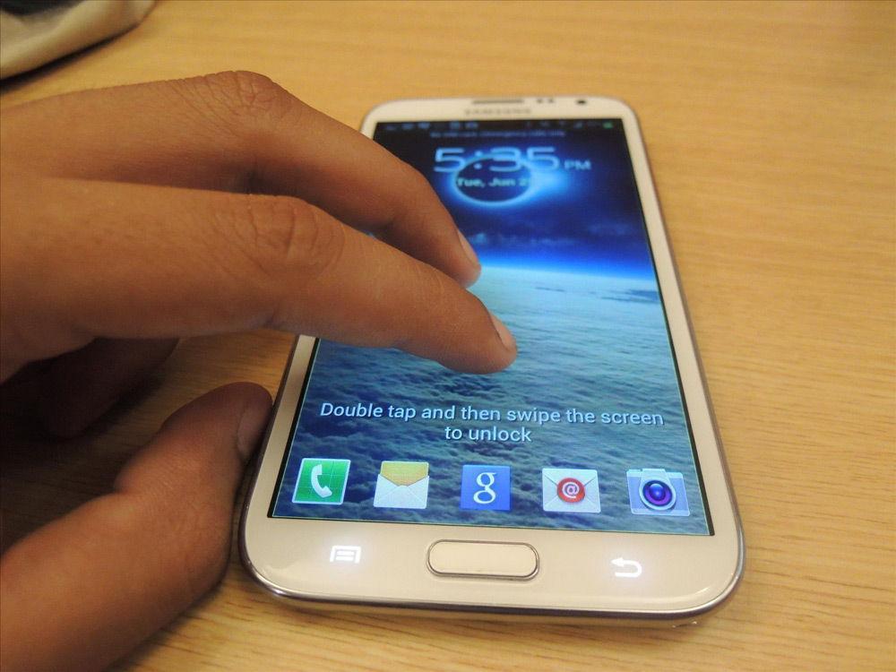 Рука двумя пальцами касается экрана смартфона